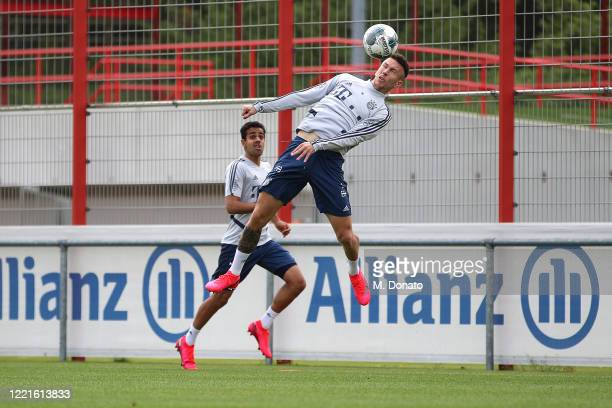 Ivan Perisic of FC Bayern Muenchen jumps for a header next to Sarpreet Singh during a training session at Saebener Strasse training ground on April...