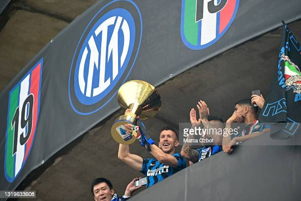 Ivan Perisic of FC Internazionale lifts the trophy towards the fans who are gathering outside the ground after the Serie A match between FC...