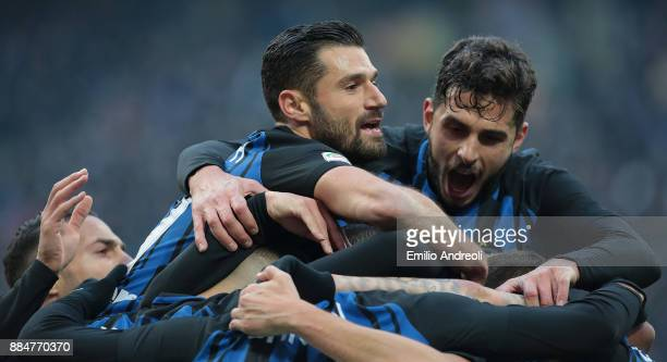 Ivan Perisic of FC Internazionale Milano celebrates with his teammate Antonio Candreva and Andrea Ranocchia after scoring the opening goal during the...