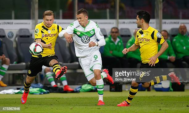Ivan Perisic of Wolfsburg is challenged by Marcel Schmelzer and Ilkay Guendogan of Dortmund during the DFB Cup Final match between Borussia Dortmund...