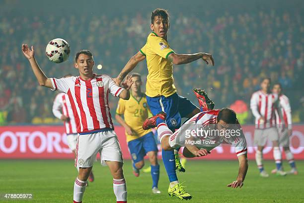 Ivan Piris of Paraguay fights for the ball with Roberto Firmino of Brazil during the 2015 Copa America Chile quarter final match between Brazil and...