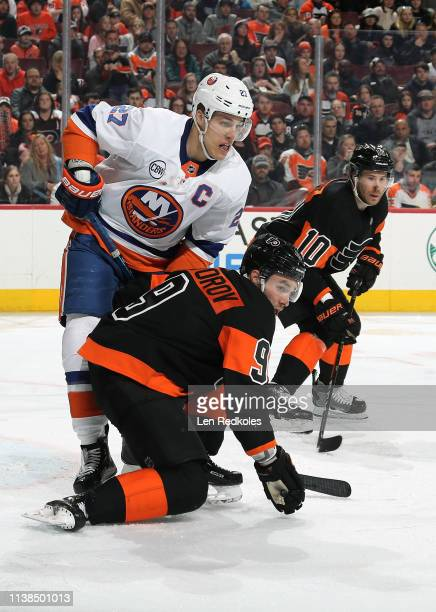 Ivan Provorov and Corban Knight of the Philadelphia Flyers battle against Anders Lee of the New York Islanders on March 23 2019 at the Wells Fargo...