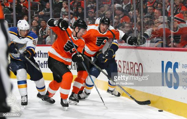 Ivan Provorov and Jori Lehtera of the Philadelphia Flyers battle for the puck along the boards against Scottie Upshall of the St Louis Blues on...