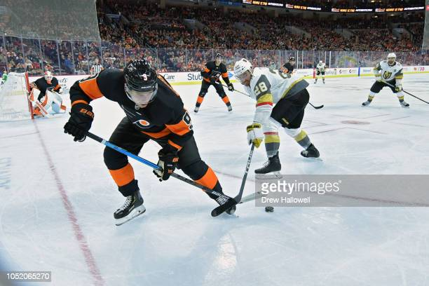Ivan Provorov of the Philadelphia Flyers and William Carrier of the Vegas Golden Knights fight for the puck at the Wells Fargo Center on October 13...