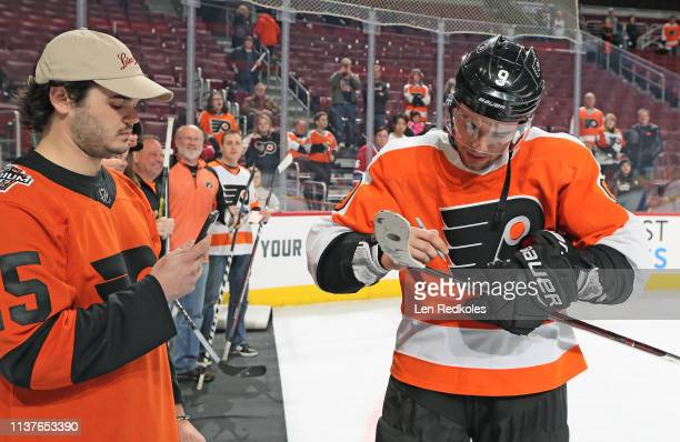 Ivan Provorov of the Philadelphia Flyers autographs his game used stick during a postgame event for Fan Appreciation Night on March 19 2019 at the...