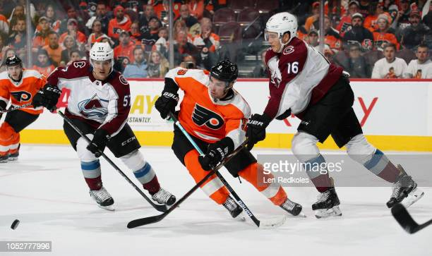 Ivan Provorov of the Philadelphia Flyers battles for the loose puck with Gabriel Bourque and Nikita Zadorov of the Colorado Avalanche on October 22...