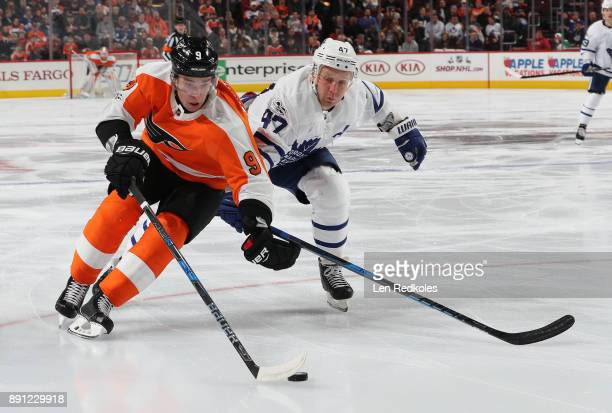 Ivan Provorov of the Philadelphia Flyers controls the puck while being pursued by Leo Komarov of the Toronto Maple Leafs on December 12 2017 at the...
