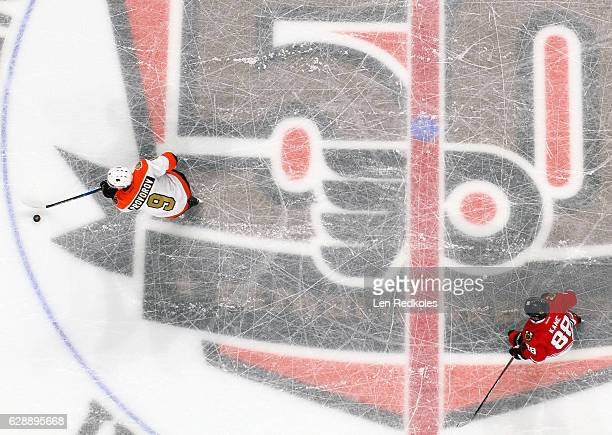 Ivan Provorov of the Philadelphia Flyers skates the puck through center ice against Patrick Kane of the Chicago Blackhawks on December 3 2016 at the...