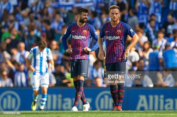 Ivan Rakitic and Gerard Pique of FC Barcelona reacts after being scored by Aritz Elustondo of Real Sociedad during the La Liga match between Real...