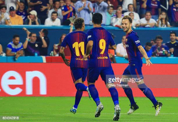 Ivan Rakitic of Barcelona celebrates his goal with teammates Neymar and Luis Suarez in the first half against the Real Madrid during their...