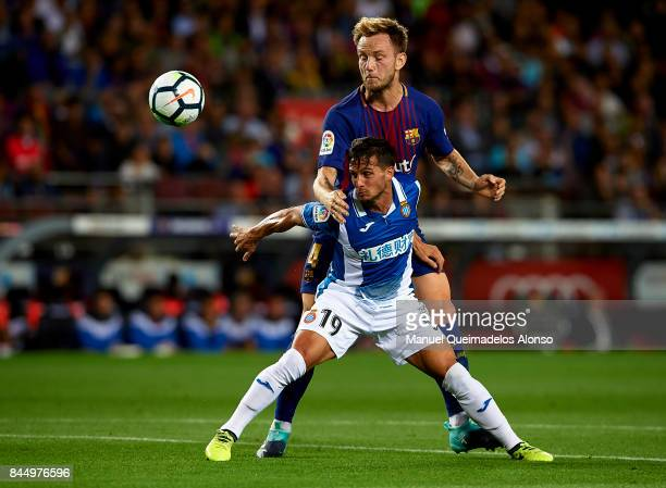 Ivan Rakitic of Barcelona competes for the ball with Pablo Piatti of Espanyol during the La Liga match between Barcelona and Espanyol at Camp Nou on...