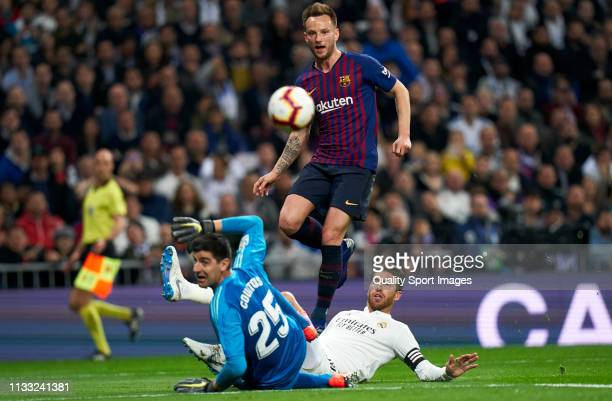 Ivan Rakitic of Barcelona scores his sides first goal past Thibaut Courtois and Sergio Ramos of Real Madrid during the La Liga match between Real...