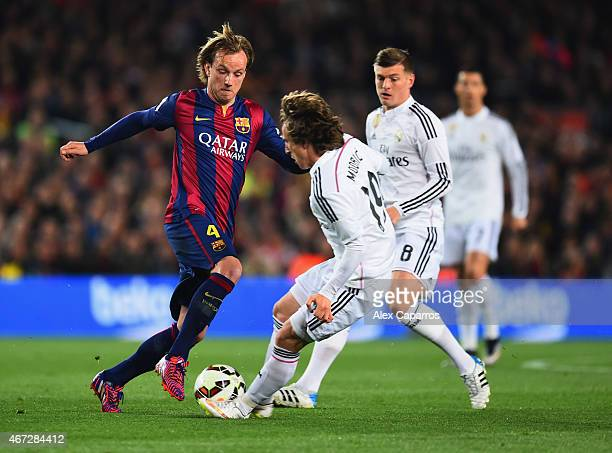 Ivan Rakitic of Barcelona takes on Luka Modric and Toni Kroos of Real Madrid CF during the La Liga match between FC Barcelona and Real Madrid CF at...