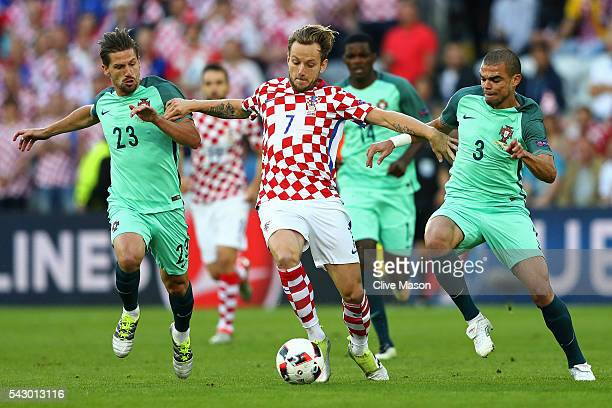 Ivan Rakitic of Croatia competes for the ball against Adrien Silva and Pepe of Portugal during the UEFA EURO 2016 round of 16 match between Croatia...