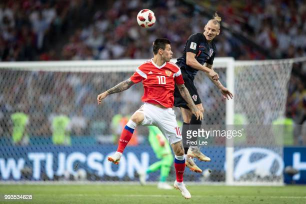 Ivan Rakitic of Croatia jump for the all with Fedor Smolov of Russia during the 2018 FIFA World Cup Russia Quarter Final match between Russia and...