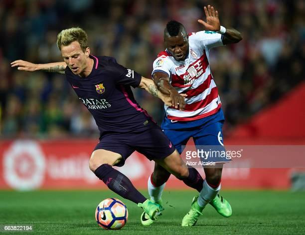 Ivan Rakitic of FC Barcelona competes for the ball with Wakaso Mubarak of Granada CF during the La Liga match between Granada CF v FC Barcelona at...