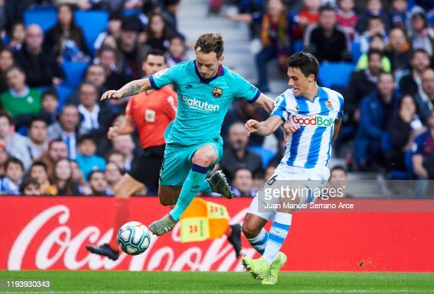 Ivan Rakitic of FC Barcelona duels for the ball with Ander Guevara of Real Sociedad during the Liga match between Real Sociedad and FC Barcelona at...