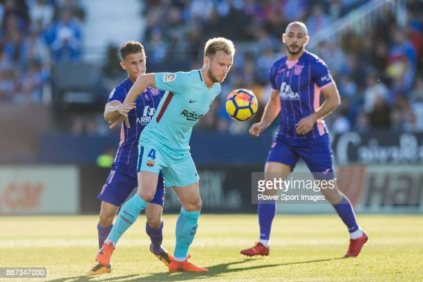 Ivan Rakitic of FC Barcelona fights for the ball with Alexander Szymanowski of CD Leganes during the La Liga 201718 match between CD Leganes vs FC...