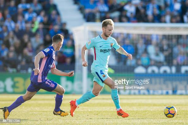Ivan Rakitic of FC Barcelona is followed by Alexander Szymanowski of CD Leganes during the La Liga 201718 match between CD Leganes vs FC Barcelona at...
