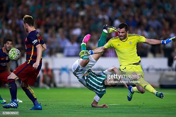 Ivan Rakitic of FC Barcelona passes goalkeeper Antonio Adan of Real Betis Balompie and his teammate German Pezzella prior to score his opening goal...