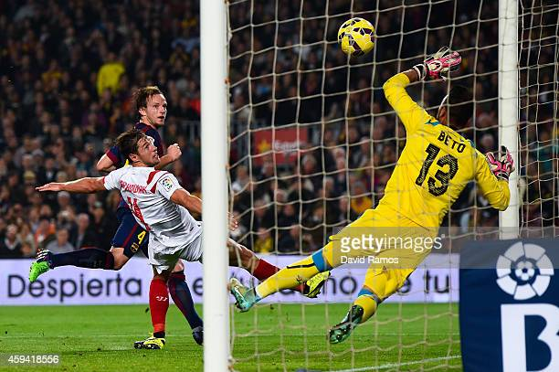 Ivan Rakitic of FC Barcelona scores his team's third goal under a challenge by Grzegorz Krychowiak of Sevilla FC during the La Liga match between FC...