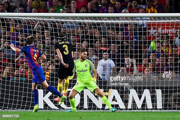 Ivan Rakitic of FC Barcelona scores the opening goal past Filipe Luis and the goalkeeper Jan Oblak of Club Atletico de Madrid during the La Liga...