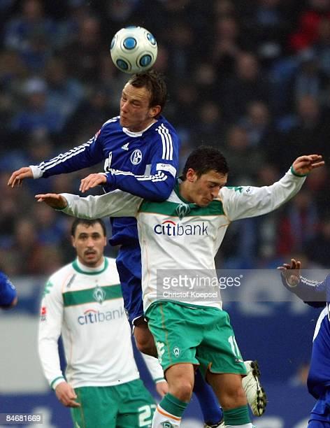Ivan Rakitic of Schalke and Mesut Oezil of Bremen go up for a header during the Bundesliga match between FC Schalke 04 and Werder Bremen at the...