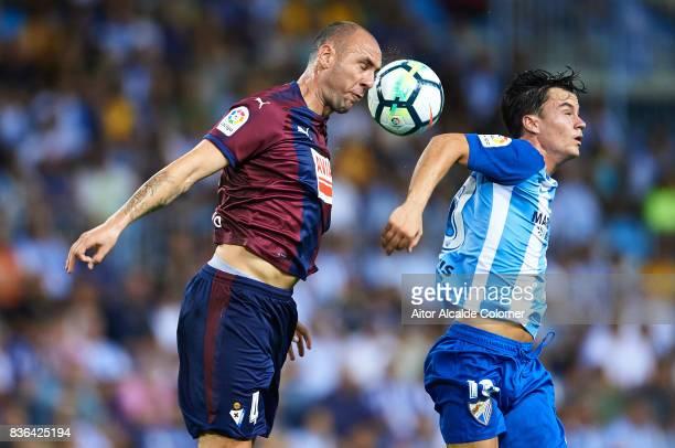 Ivan Ramis of SD Eibar competes for the ball with Juan Pablo Anor Juanpi of Malaga CF during the La Liga match between Malaga and Eibar at Estadio La...