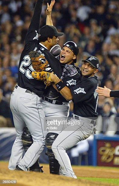 Ivan Rodriguez of the Florida Marlins celebrates with teammates Derrek Lee and Alex Gonzalez after defeating the New York Yankees 20 in game six of...