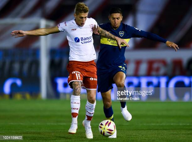 Ivan Rossi of Huracan fights for the ball with Agustin Almendra of Boca Juniors fight for the ball during a match between Huracan and Boca Juniors as...