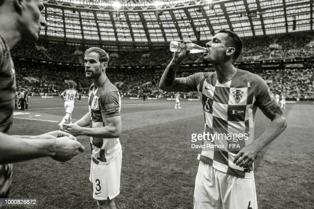 Ivan Strinic and Dejan Lovren of Croatia drinks water prior to the kick off during the 2018 FIFA World Cup Russia Final between France and Croatia at...