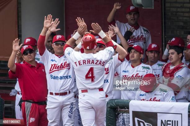 Ivan Terrazas of Diablos celebrates with his teammates after hitting a home run during a match between Pericos de Puebla and Diablos Rojos as part of...