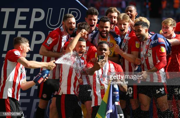 Ivan Toney of Brentford is sprayed with champagne as he takes a selfie photo with his team mates as they celebrate winning the Sky Bet Championship...