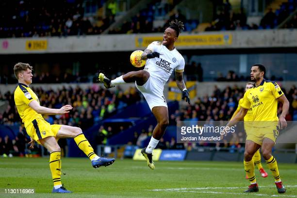 Ivan Toney of Peterborough United controls the ball in the air under pressure from Rob DIckie and Curtis Nelson of Oxford United during the Sky Bet...