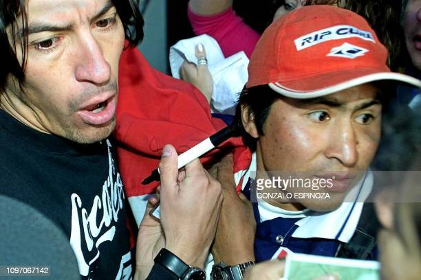Ivan Zamorano captain of the Chilean soccer team signs an autograph to a fan after a practice of his team in La Paz Bolivia 17 July 2000 El capitan...