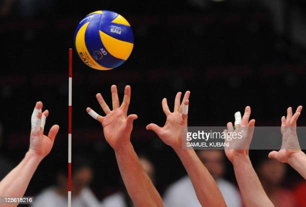 Ivan Zaytsev of Italy spikes the ball over the net as Lukasz Tomas Zygadlo and Piotr Nowakowski of Poland attempts to block it during the European...