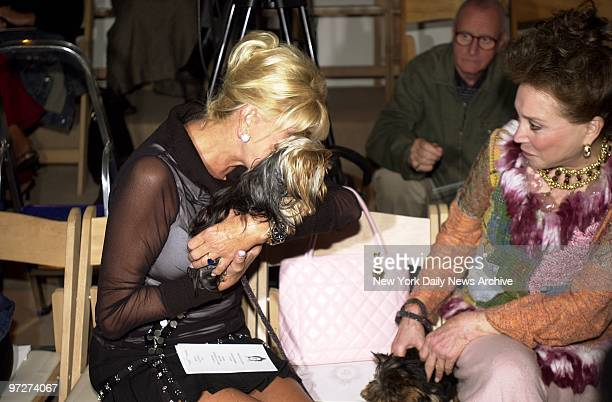 Ivana Trump cuddles one of Cindy Adams' Yorkshire terriers as the two women take in a showing of Zang Toi's spring 2004 collection at Bryant Park...