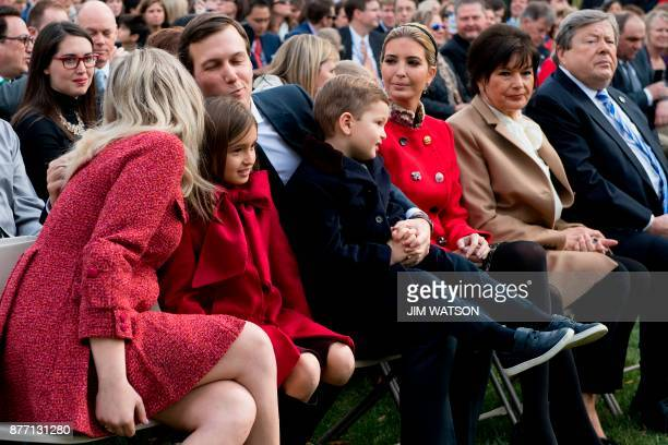 Ivanka Trump looks on as Tiffany Trump kisses brother in law and Senior Advisor to the President Jared Kushner as they sit with Trump's grandchildren...