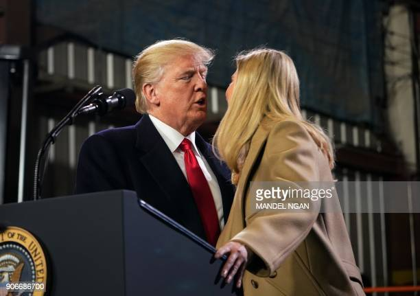 Ivanka Trump receives a kiss from her father US President Donald Trump following a tour of the HK Equipment Company in Coraopolis Pennsylvania on...