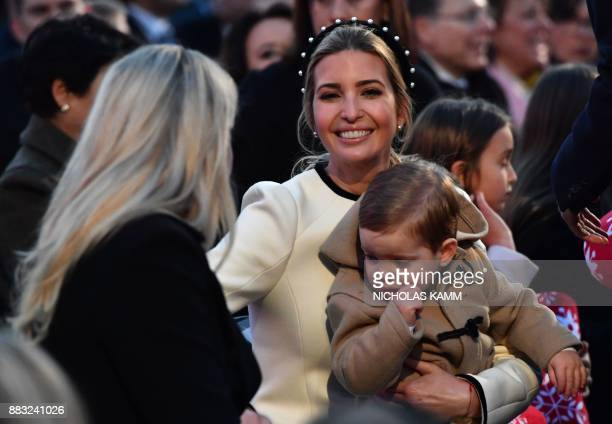 Ivanka Trump smiles at Tiffany Trump while holding her son Theodore James Kushner before the arrival of US President Donald Trump for the 95th annual...