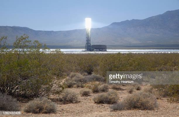 ivanpah solar power facility showing one boiler/receiver; mountains, blue sky beyond - timothy hearsum stockfoto's en -beelden