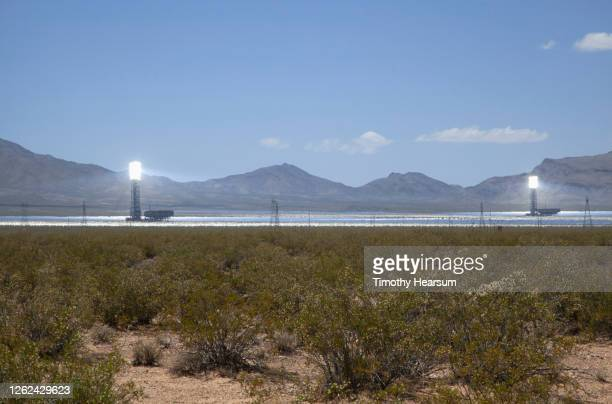 ivanpah solar power facility showing two boilers/receivers; mountains, blue sky beyond - timothy hearsum stockfoto's en -beelden