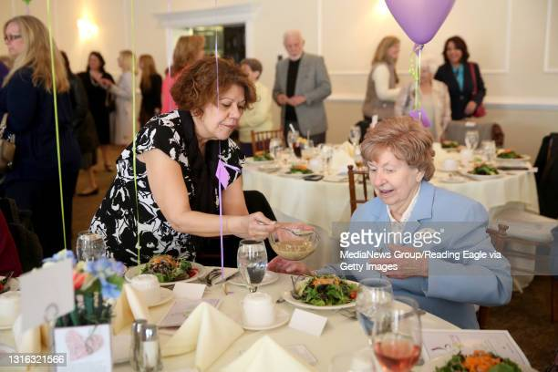 Ivette Belez, of Mary's Shelter, helps Sister Eileen Kantz, MSC, of Sacred Heart Villa, put dressing on her salad during the Spring into Mission Gala...
