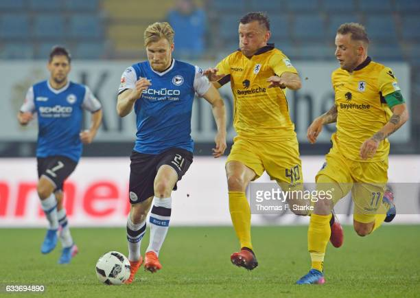 Ivica Olic and Daniel Adlung of Munich tackle Andreas Voglsammer of Bielefeld during the Second Bundesliga match between DSC Arminia Bielefeld and...