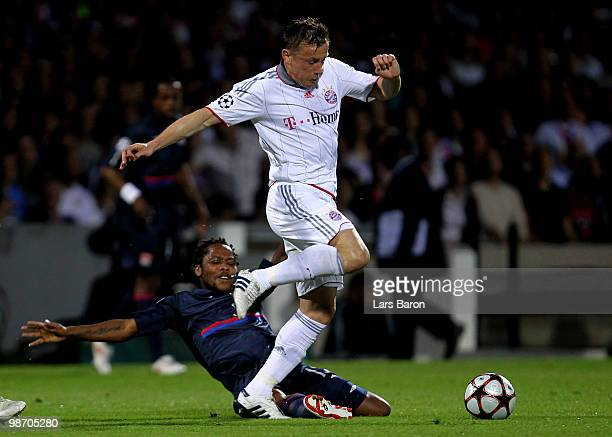 Ivica Olic of Bayern Muenchen is tackled by Jean Makoun of Olympique Lyonnais during the UEFA Champions League semi final second leg match between...