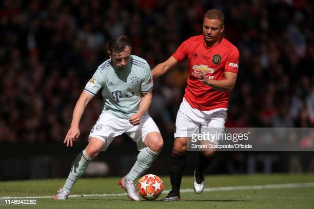 Ivica Olic of Bayern Munich battles with Wes Brown of Man Utd during the Treble Reunion friendly match between the Manchester United '99 Legends and...
