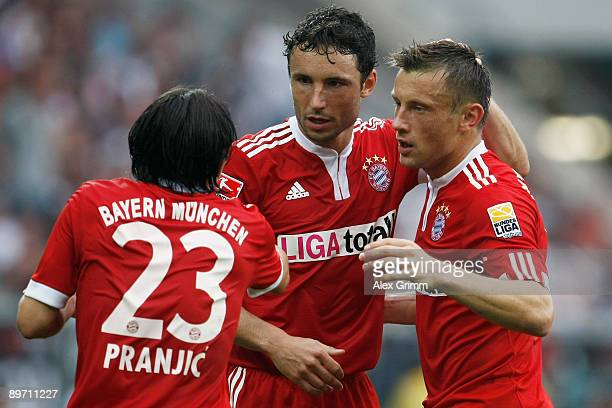 Ivica Olic of Muenchen celebrates his team's first goal with team mates Mark van Bommel and Danijel Pranjic during the Bundesliga match between 1899...
