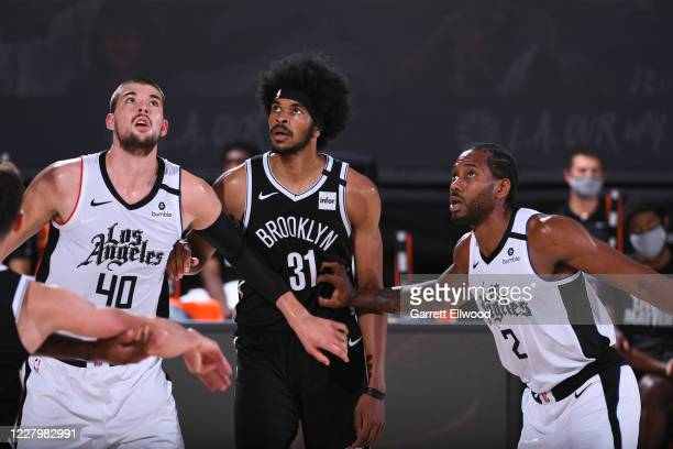 Ivica Zubac and Kawhi Leonard of the LA Clippers fight for position against Jarrett Allen of the Brooklyn Nets during the game on August 9 2020 at...