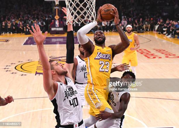 Ivica Zubac and Patrick Beverley of the Los Angeles Clippers defend LeBron James of the Los Angeles Lakers as he goes for a basket in the first half...