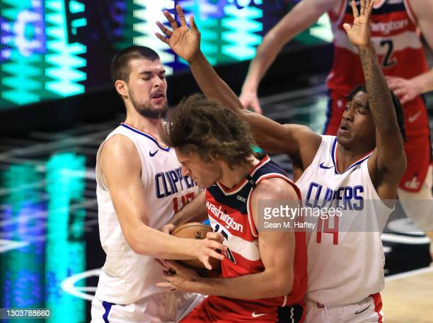 Ivica Zubac and Terance Mann of the LA Clippers defend against Robin Lopez of the Washington Wizards during the second half of a game at Staples...